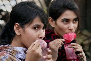 Nagpur: Girls enjoy chuski to beat the heat on a hot summer day in Nagpur on Friday. PTI Photo(PTI4_29_2016_000049A)